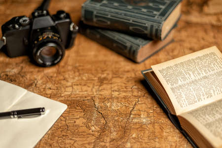 old expedition map with notebook, other books and vintage film camera Reklamní fotografie - 117204284