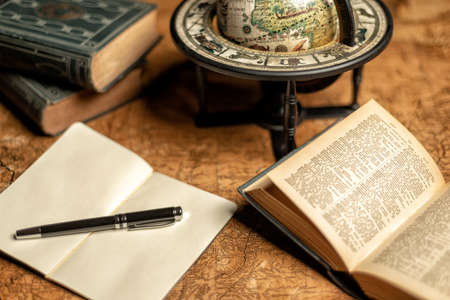 old expedition map with notebook, other books and vintage globe