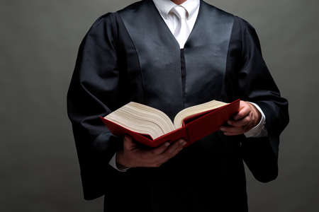 german lawyer with a classical black robe, white tie and book Stock Photo - 120987882