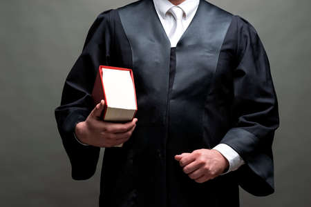 german lawyer with a classical black robe, white tie and book