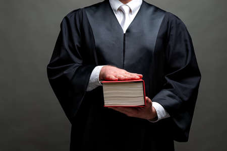 deutscher Anwalt mit klassischer schwarzer Robe, weißer Krawatte und Buch Standard-Bild