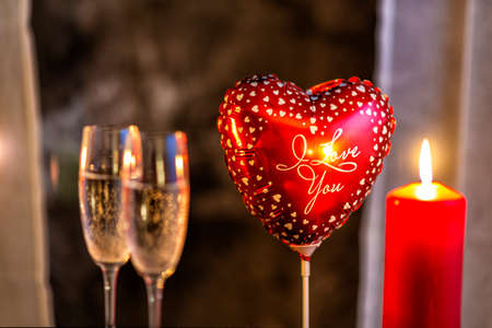 heart balloon, candle and champagne glasses on Valentines day