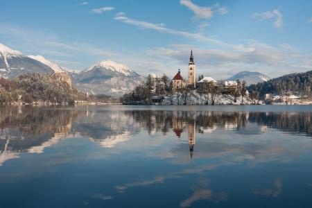 Blick auf Lake Bled mit kleinen Insel mit Kirche und Burg auf Felsen in Slowenien, Europa.