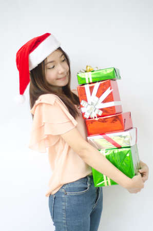 Santa woman showing gift wearing Santa hat  Christmas woman portrait of a cute, beautiful smiling Asian model  Isolated on white background photo