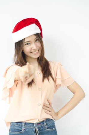 Young beauty Asian girl with santa hat point her finger to you  photo