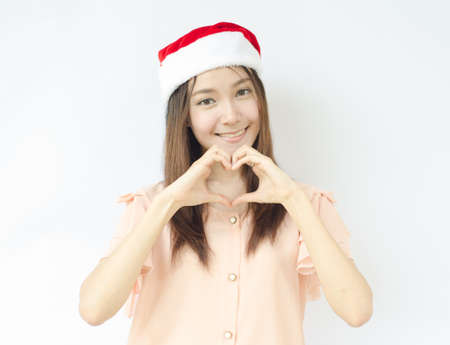 A portrait of beautiful Asian santa woman making heart sign photo