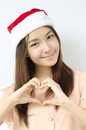 A portrait of beautiful Asian santa woman making heart sign photo