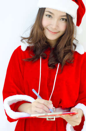 A Portrait of beautiful Asian santa woman writing note  photo