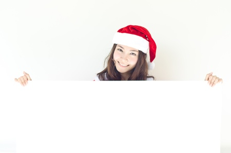 Asian Christmas woman wearing Santa hat over billboard sign, isolated on white background   photo