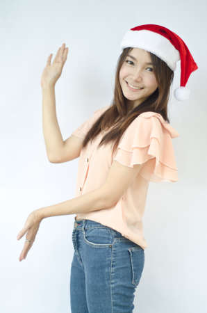 Smiley Asian woman in santa hat with empty copyspace on open hand  photo