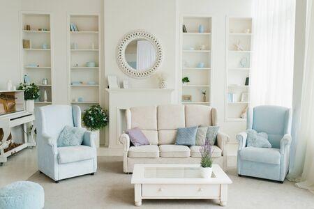 Klasyczny salon w odcieniach błękitu i bieli. Sofa, fotele, kominek, stolik kawowy i lustro w domu