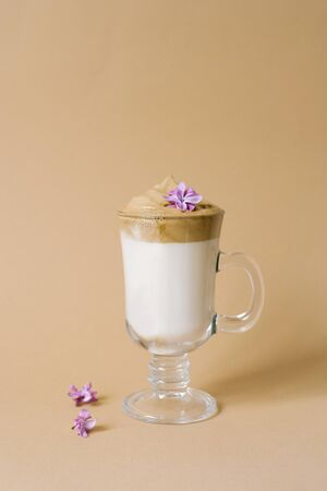 Beautiful dalgon coffee drink with foam in a transparent Cup and lilac flowers on a beige background. Copy space Imagens