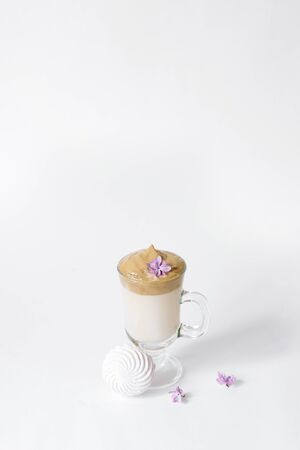 Dalgon's trending drink is coffee. Coffee mug, lilac and marshmallow on a white background. Copying space
