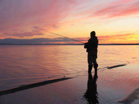Sunset at river Ob at Polar circle with silhouette of a fisherman photo