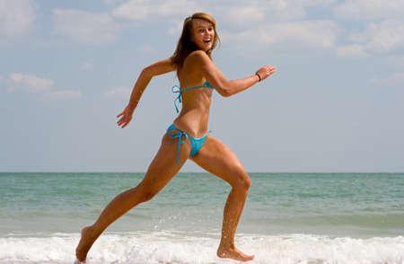A cheerful girl running at a beach photo