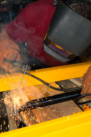Welder welding a metal part in an industrial environment, wearing standard protection equipment. photo