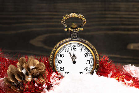 New Year clock. Decorated with gold cone on snow. Stock Photo