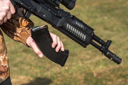 A man is holding a rifle magazine camouflage clothes
