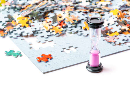 Pink and black sand hourglass on color puzzle pieces white background Banco de Imagens