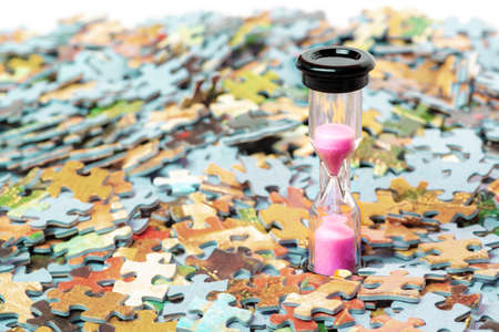 Pink and black sand hourglass on color puzzle pieces background