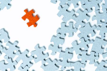 Puzzle pieces around one bright piece white background