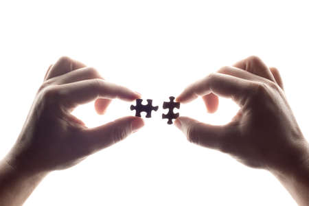 Two hands are trying to connect a puzzle pieces white background