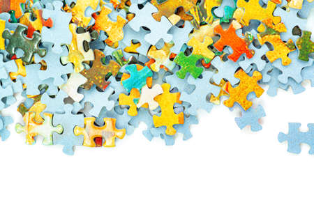 Many bright puzzle pieces separated light blue base white background. Banco de Imagens