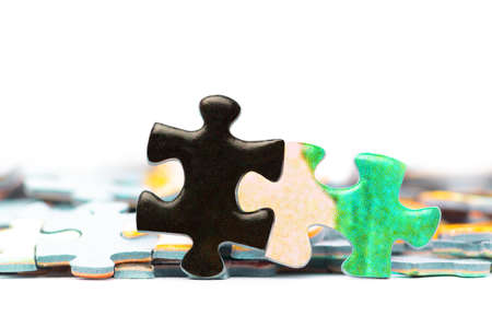 Two bright puzzle pieces connected in front of separated pieces. White background.