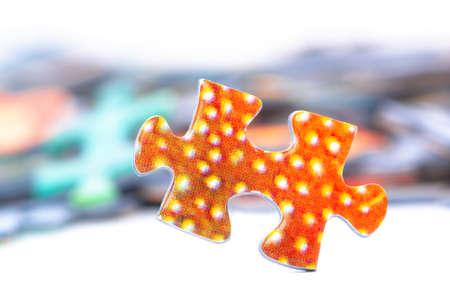 Bright orange puzzle piece dots closeup white background