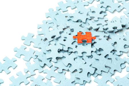 Bright orange puzzle piece and many light blue puzzle pieces background