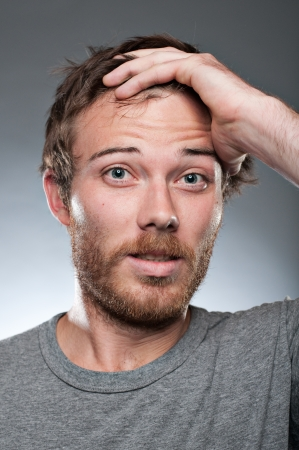 frowning: A Caucasian man in his 20s with his hand in his hair looking worried. Stock Photo
