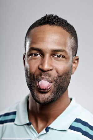 An African American man in his 20s sticking out his tongue. photo