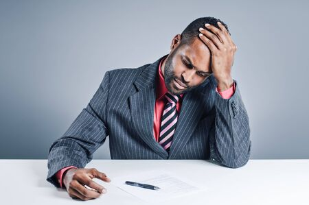 african businessman: A young African American businessman signing a contract. Stock Photo