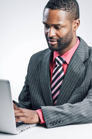 african businessman: Studio shot of a young African American Businessman using a laptop computer. Stock Photo