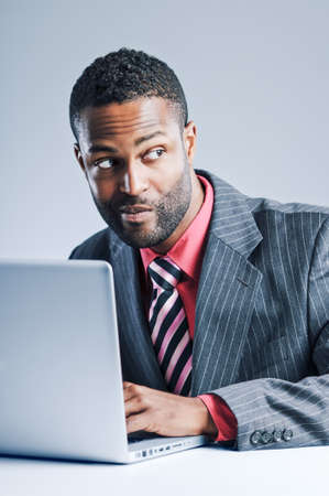 sneaky: Studio shot of a young African American Businessman using a laptop computer. Stock Photo