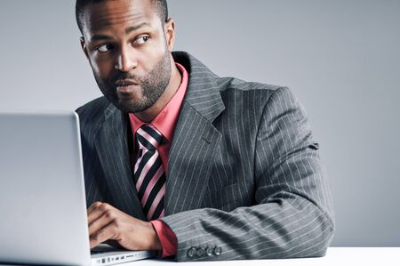 Studio shot of a young African American Businessman using a laptop computer. Stock Photo