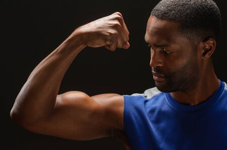 A young African American man flexing his biceps, studio shot.