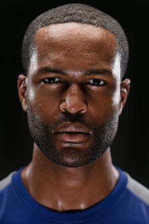 sudoracion: Un joven atleta estadounidense expresión en blanco retrato de estudio de África Foto de archivo