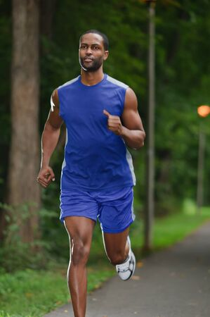 A young African American athlete running on a wooded footpath  Stock Photo - 19248569