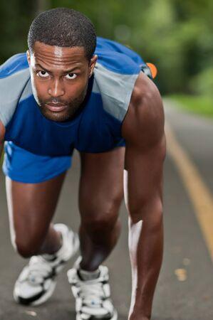 hombre deportista: Un joven atleta afroamericano que se ejecuta en un sendero boscoso
