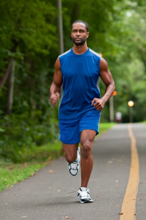 A young African American athlete running on a wooded footpath