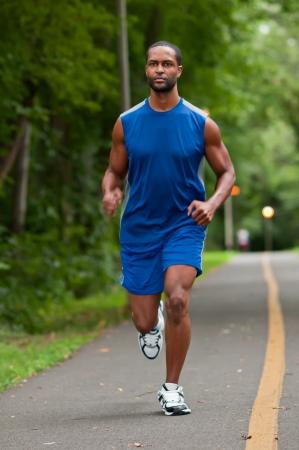 hacer footing: Un joven atleta afroamericano que se ejecuta en un sendero boscoso