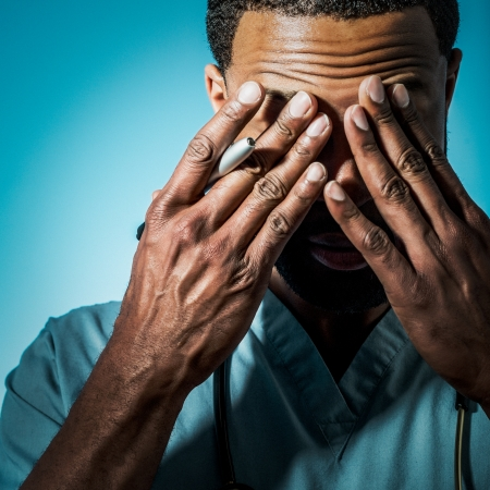 distraught: Studio shot of a young African American doctor suffering fatigue and rubbing his eyes