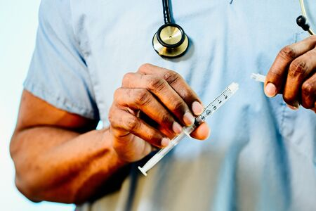A doctors hands connecting a blunt tip syringe to an IV drip  Stok Fotoğraf