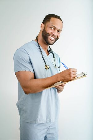 Studio shot of a young African American doctor or nurse holding a clipboard  photo