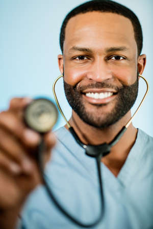 Studio shot of a young African American doctor holding up a stethoscope. photo