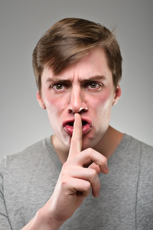 A caucasian man with his finger to his mouth shushing angrily
