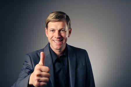 blonde yeux bleus: Un jeune homme de race blanche donnant un geste de la main positive.