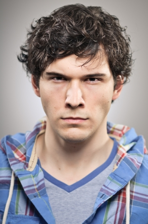 scowl: A caucasian man in his 20s with a deep scowl. Stock Photo