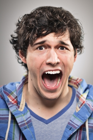 A caucasian man in his 20s screaming. photo